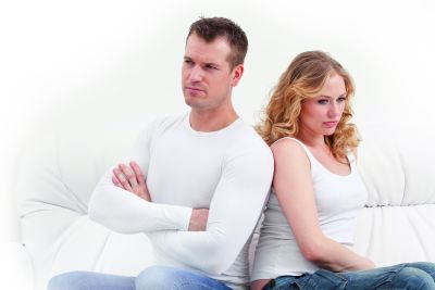 Young sad couple sitting on sofa Back to back over white