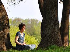 Frau schreibt Tgaebuch im Park