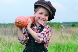 Smiling boy standing with pumpkin on his shoulder in the field
